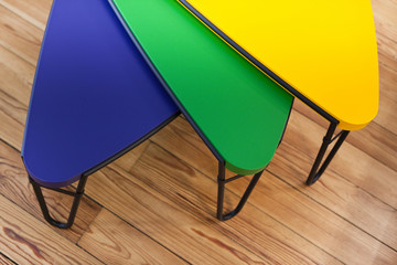 Three colorful modern tables on a wooden floor