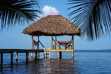 Palapa hut with thatched roof over Caribbean sea