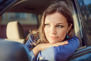 Car woman on road trip looking out of window. Having rest on sun