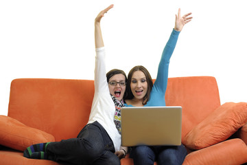 female friends working on laptop computer at home