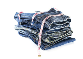 heap of jeans trousers with tape measure