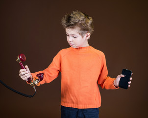 Child with retro telephone and smartphone in his hands.