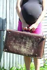 Pregnant girl with old suitcases goes through the village