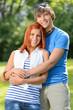 Romantic teenage couple hugging in sunny park