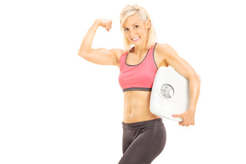 Muscular woman holding a weight scale