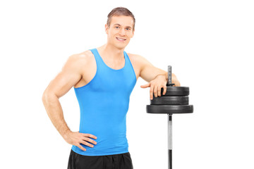 Muscular man leaning on a barbell