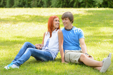 Teenage couple sitting grass looking each other