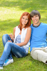 Teenage couple sitting on grass embracing summer