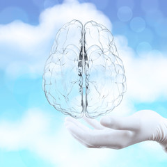 medical doctor hand showing 3d glass human brain on nature backg