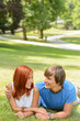 Teenage couple lying in sunny park