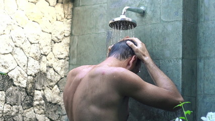Young man washing hair under shower, super slow motion