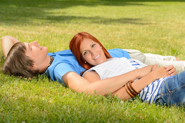 Teenage couple enjoying sun lying on grass