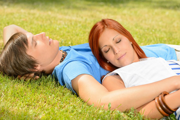 Teenage couple relaxing on grass closed eyes