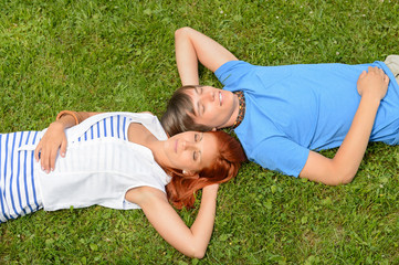 Teenage couple lying on grass