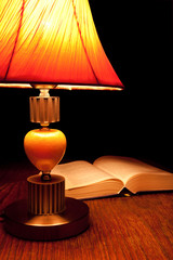 Single table-lamp and opened book