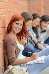 Student girl sitting outside campus with friends