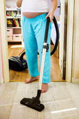 Pregnant woman hoovering