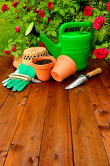 Copyspace gardening tools on wooden table and rose flowers