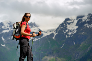 Young woman with backpack and trekking poles in mountains
