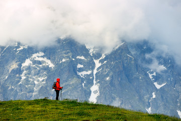 Young woman with backpack in red jacket in mountains