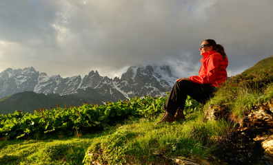 Young woman in red jacket enjoy sunset in mountains