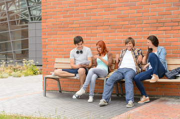 Students friends sitting bench outside campus