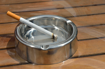 Metal ashtray with a cigarette on a wooden table