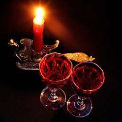 red candle in vintage candlestick and wineglasses