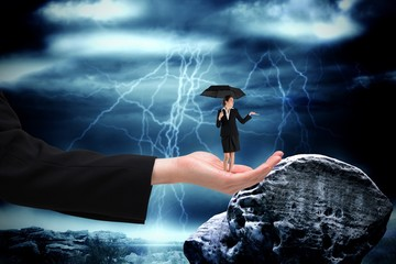 Composite image of young businesswoman holding umbrella in large