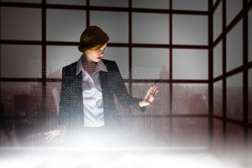 Composite image of redhead businesswoman using interactive desk