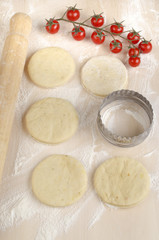 mini pizza dough on a floury wooden board