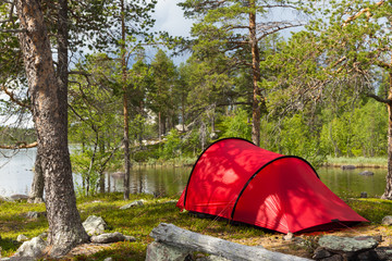 Campsite with a red tent at a lake.
