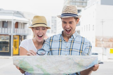 Young tourist couple consulting the map with magnifying glass