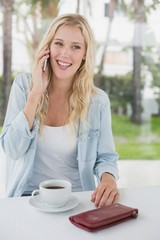 Pretty blonde sitting at table having coffee talking on phone