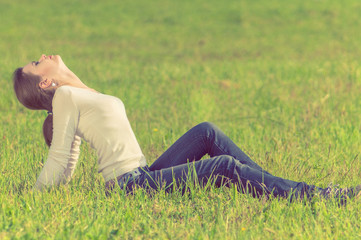 background girl sitting  on green grass arching her back and eye