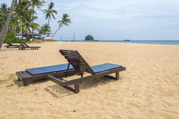 Wooden lounge with clean sand at tropical island