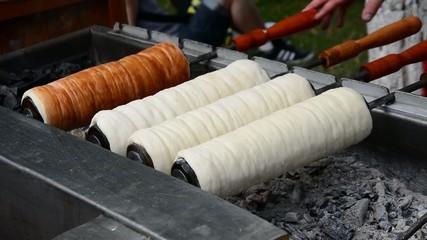 Kürtőskalács, chimney cake baking over charcoal fire outdoors.