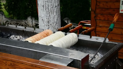 Kürtőskalács, chimney cake baking over charcoal fire outdoors.