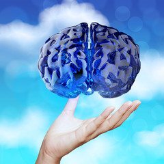 medical doctor hand showing 3d blue glass human brain on nature