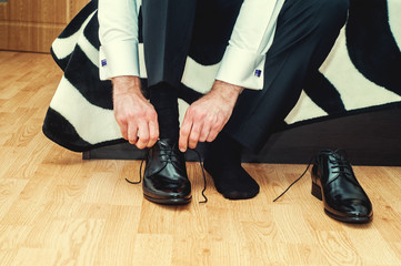 Groom wearing shoes on wedding day, tying the laces