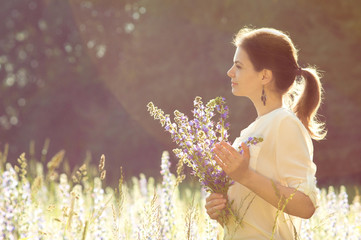 summer background girl in a field with flowers in their hands in