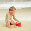 little girl playing  with toys sand set  on the beach