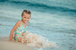 happy little girl splashing in the sea