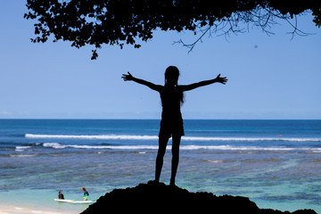 silhouette of the teen girl standing on the beach at  the day ti