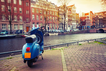 Blue scooter stands parked on the canal coast in Amsterdam. Inst