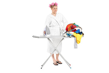 Woman in bathrobe ironing a pile of clothes
