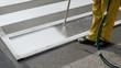 Worker spraying of pedestrian crosswalk at a street