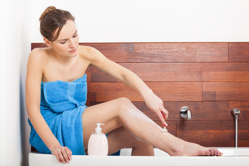 Beautiful woman shaving legs