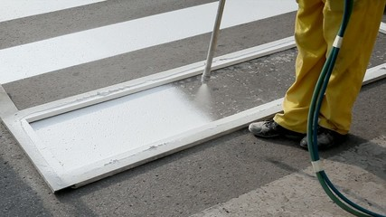 Worker spraying of pedestrian crosswalk at a street