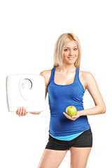 Young woman holding an apple and a weight scale